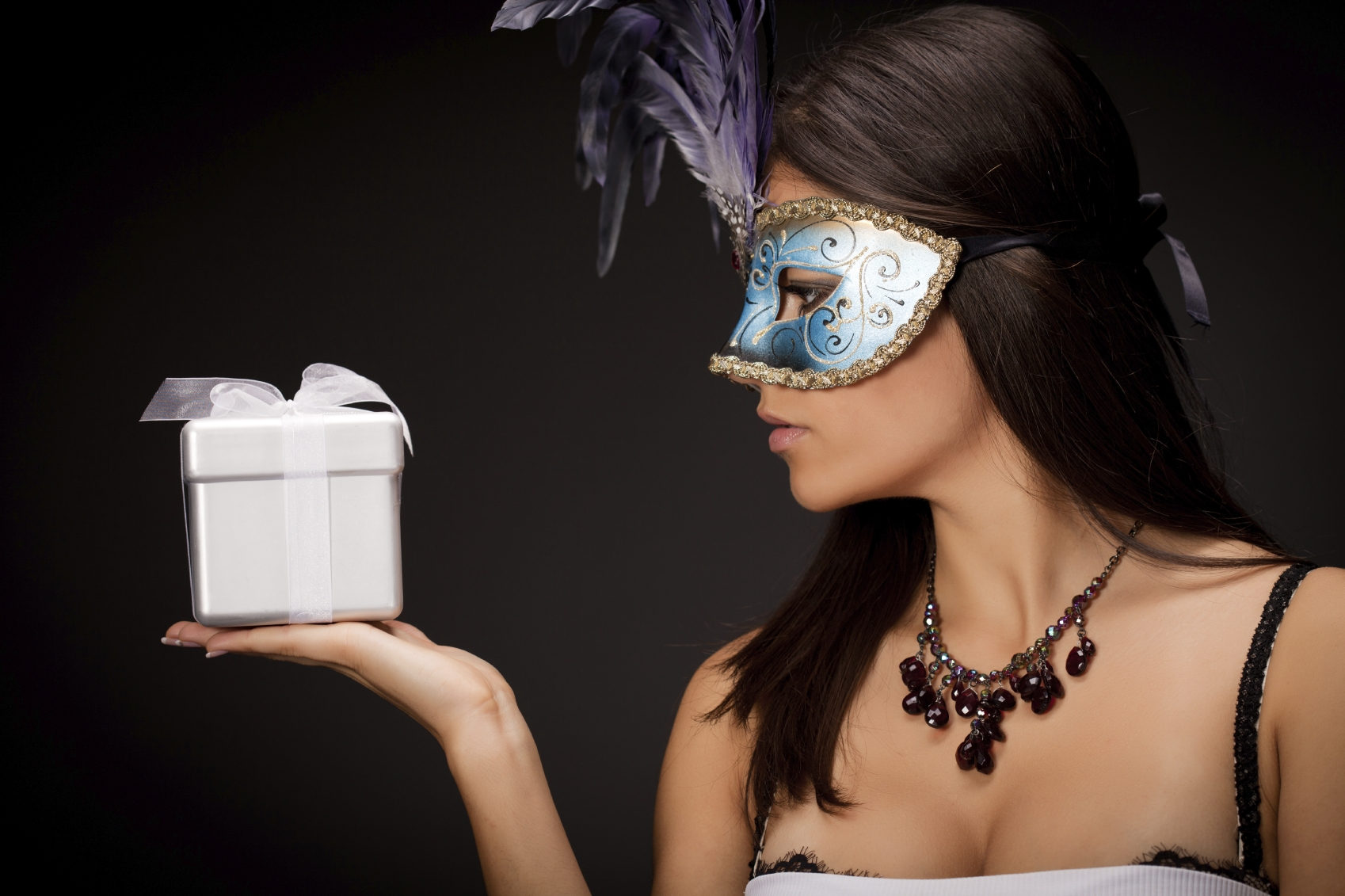 Beautiful mysterious young woman with mask holding a silver gift box .