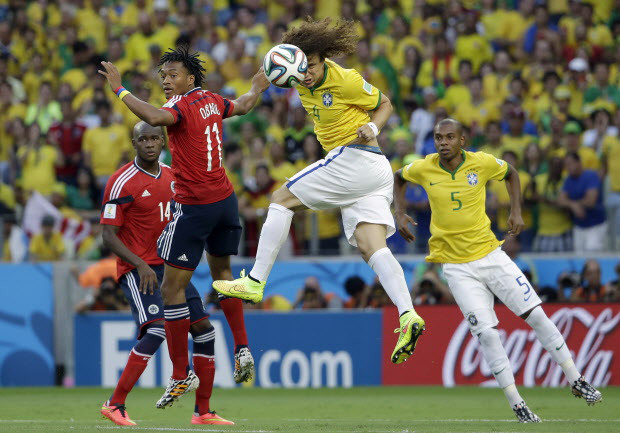 Brazil's David Luiz head the ball next to Colombia's Juan Cuadrado during the World Cup quarterfinal soccer match between Brazil and Colombia at the Arena Castelao in Fortaleza, Brazil, Friday, July 4, 2014. (AP Photo/Hassan Ammar)