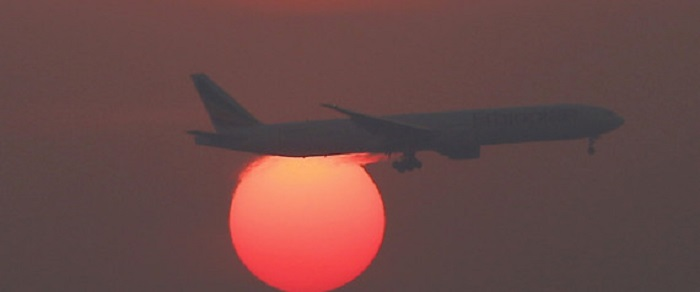 A plane flies over the setting sun in the sky at Beijing International Airport, China, March 2, 2016.  REUTERS/Kim Kyung-Hoon/File Photo